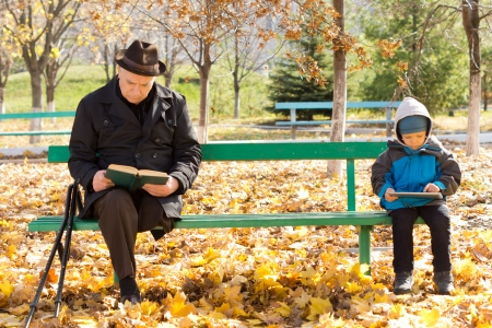overcoat: Elderly handicapped man on crutches and a small boy sitting on a park bench in the autumn sun each engrossed in reading a book and tablet-pc