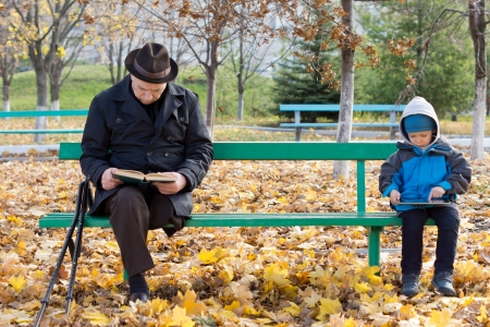 Senior man on crutches reading a book with his little grandson sitting on the opposite end of the wooden park bench playing on a tablet computer photo