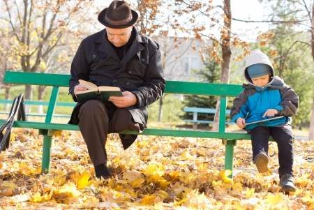 Grandfather and grandson amusing themselves reading together in the autumn sunshine sitting on a park bench with the old man reading a printed book and the child an e-book on his tablet-pc photo