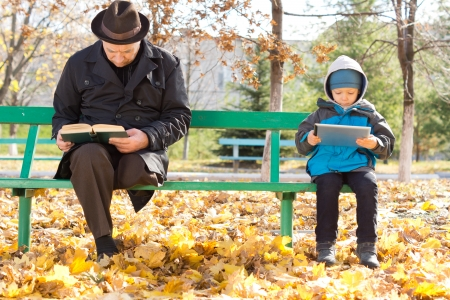Elderly man reading his book and a small boy looking at his tablet computer sit ignoring each other at either end sharing a park bench on a cold autumn day photo