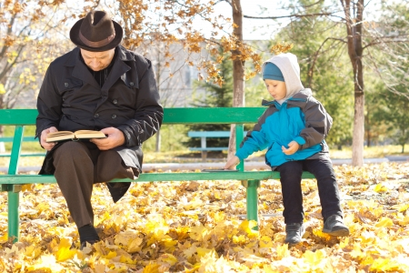 Cute little boy playing alongside his grandfather as the two sit together on a park bench in the autumn sunshine dressed in warm clothing photo