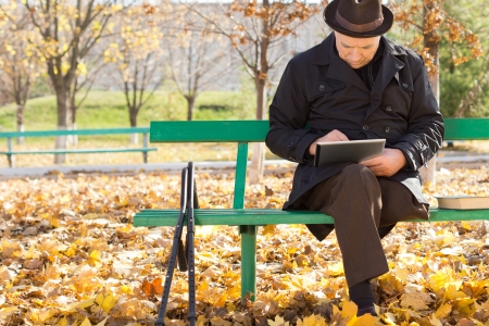 Elderly man on crutches using a tablet computer as he sits outdoors in the sunshine in a warm overcoat on a chilly autumn day photo