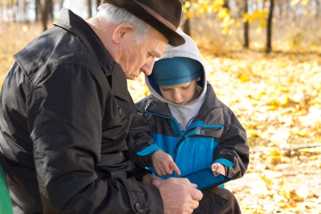 overcoat: Grandfather and grandson sharing a tablet computer sitting close together on a park bench browsing the internet