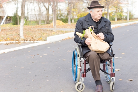 Elderly man in a wheelchair bring home the groceries from the supermarket in a brown paper bag as he sits waiting in the street for assistance photo