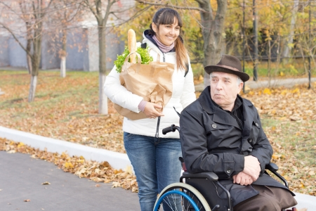 Woman helping an elderly disabled man with his grocery shopping pushing his wheelchair along the street and carrying his bag of purchases