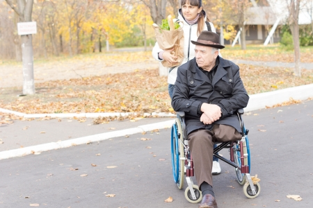 Senior disabled man being helped with his shopping sitting in his wheelchair as a female carer or daughter pushes him along the street carrying his groceries photo