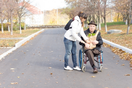 Daughter handing an elderly disabled man in a wheelchair a bag of groceries as she prepares to push him along the street after taking him shopping photo