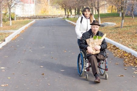 Senior handicapped man with a female carer being pushed along the street in his wheelchair as he holds a bag of groceries on his lap photo