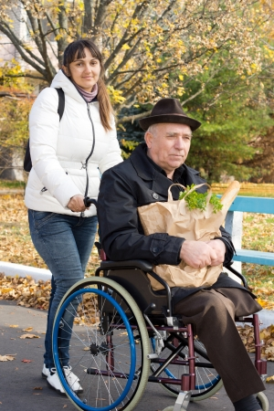 overcoat: Smiling woman helping her disabled elderly father taking him out grocery shopping pushing him along the street in his wheelchair