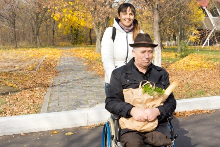 Helpful woman pushing a senior man in a wheelchair as they cross the street from an autumn park with a large packet of fresh groceries from the shop photo