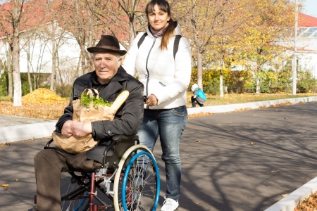 Ayuda de la mujer mayor que ella padre minusv�lidos empuj�ndolo a lo largo de la calle en su silla de ruedas, ya que volver a hacer sus compras de comestibles