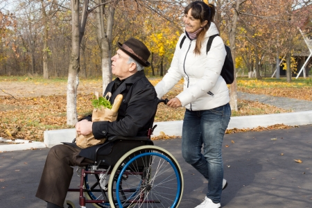 pushes: Happy woman helping a disabled elderly man as she pushes his wheelchair along a road on their return from doing the grocery shopping Stock Photo