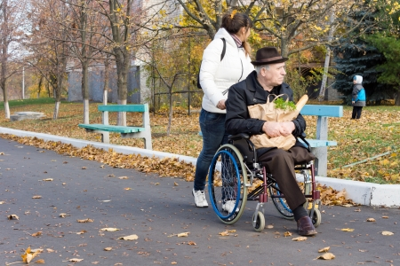 Female carer pushing a disabled man in a wheelchair with his groceries along the street turning to watch a young child playing in the park alongside photo