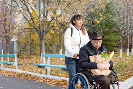Attractive casual middle-aged woman taking an elderly disabled man grocery shopping in his wheelchair pushing him along the road with his bag of groceries photo