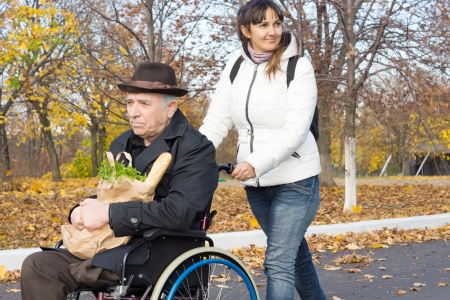 Smiling female carer pushing an old handicapped man in a wheelchair along the street as they return from doing his grocery shopping photo