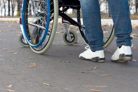 スニーカーとジーンズを身に着けている通りの車椅子を押す人の後部から低角度表示