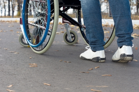 Low angle view from the rear of a person pushing a wheelchair along the street wearing sneakers and jeans