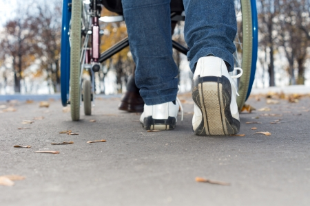 Low angle view of the feet of a person in jeans and sneakers pushing a wheelchair down the street 版權商用圖片