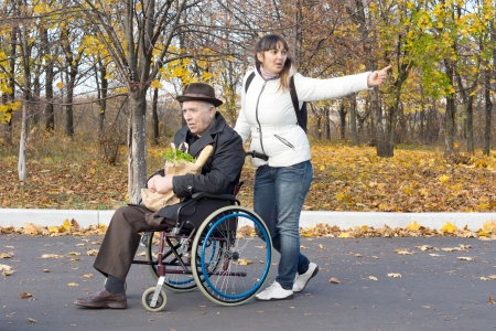 Woman pushing an elderly man in a wheelchair stretching out her arm pointing to something and calling out as they walk along the street photo