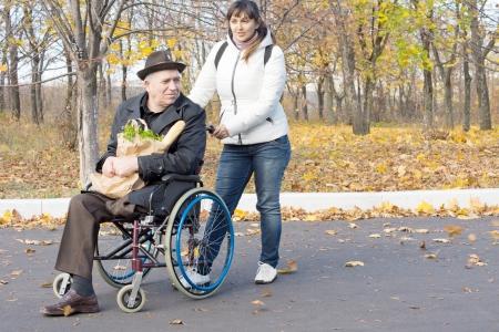 Mujer ayudar a un jubilado con discapacidad en silla de ruedas empuj�ndolo a lo largo de la calle en su silla de ruedas como �l agarra una bolsa de papel llena de comestibles en su regazo