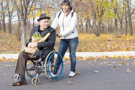 overcoat: Woman helping a disabled pensioner in a wheelchair pushing him along the street in his wheelchair as he clutches a paper bag filled with groceries on his lap Stock Photo