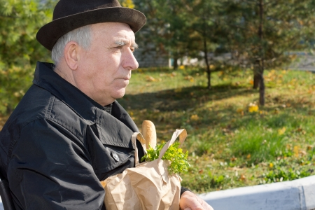 contented: Elderly pensive man in an overcoat and hat sitting with a bag of groceries on his lap in the sunshine, close up side view portrait Stock Photo