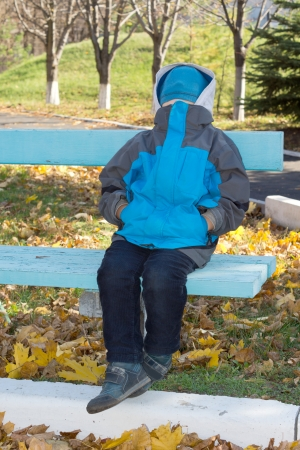 anorak: Little boy sitting on a wooden park bench with a knitted blue beanie cap concealing his face and the jacket of his anorak pulled up high so that he is unrecognisable