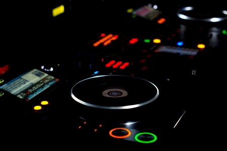 DJ turntable and music deck illuminated at night with colourful lights lighting up the knobs and controls for mixing audio soundtracks and recordings
