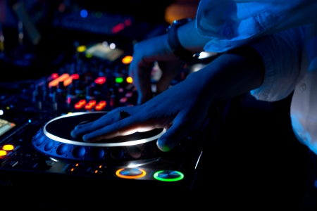 Close up view of the colourful controls on the deck at night with the hands of a DJ mixing and scratching music at a concert using vinyl records on a turntable photo