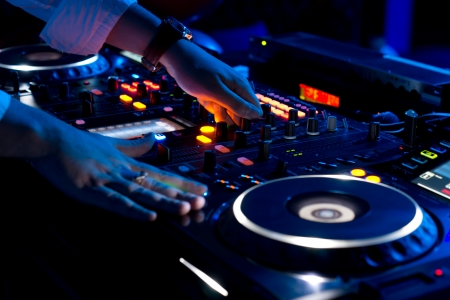 Hands of a DJ mixing music at a disco or concert with one hand on the switches and one held near the vinyl record on the turntable photo