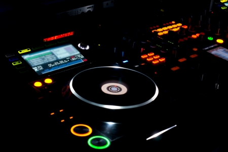 Colourful turntable and LP vinyl record on a DJ music deck at a disco, concert or party for mixing music and recorded soundtracks Фото со стока