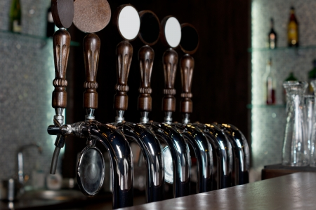 View across the counter of a row of beer taps on a stainless steel mechanical keg in a pub used to dispense draught beer photo