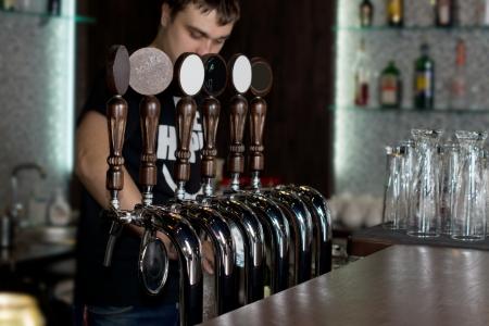 Camarero de sexo masculino joven de pie detr�s de un mostrador en un pub o club dispensar cerveza de barril