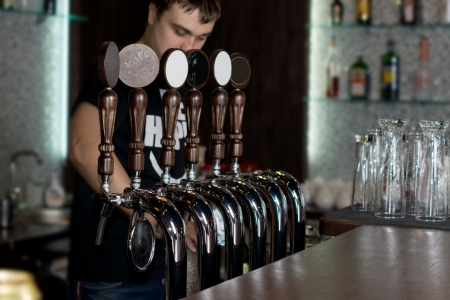 beer pump: Young male bartender standing behind a counter in a pub or club dispensing draught beer