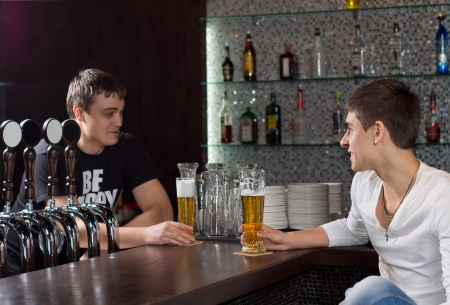 Barman standing behind the counter in a pub chatting to a customer as they enjoy a pint of beer together photo