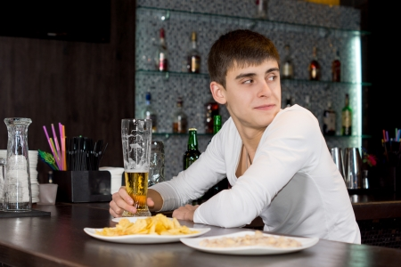 Young man sitting at a bar counter with a half drunk pint of beer looking over his shoulder waiting for his friends to arrive photo