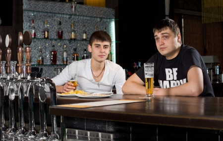 Two young teenage men drinking at the pub sitting at the counter in the bar enjoying a pint of beer photo
