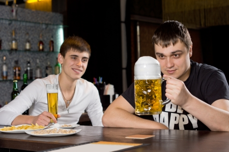 evening out: Man eyeing a large tankard of beer in anticipation as he sits with a friend enjoying an evening out together at the pub