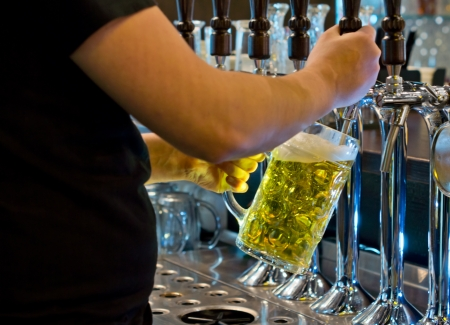 Close up view of the hands of a male bartender dispensing a large tankard of light golden draught beer from a row of spigots on a stainless steel keg photo