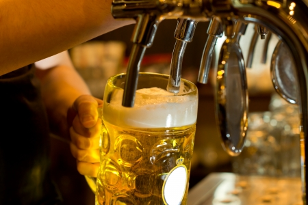 Close up of a male bartender dispensing draught beer in a pub holding a large glass tankard under a spigot attachment on a stainless steel keg 스톡 콘텐츠