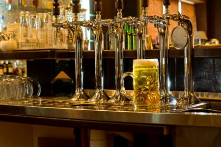 Row of stainless steel beer taps on a wooden counter for dispensing draught beer in a pub with a large glass tankard of beer alongside 스톡 콘텐츠