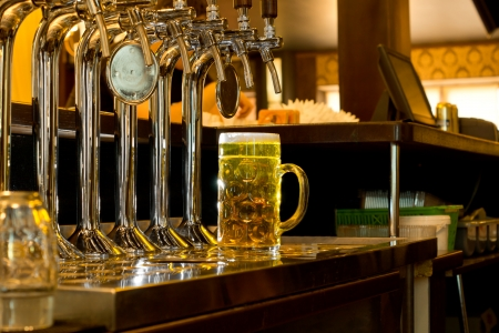 Row of taps attached to metal beer kegs in a bar for dispensing draught beer with a large glass tankard full of golden draught alongside them on the counter