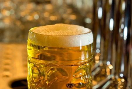 Close-up of a beer mug filled with cold foamy beer, in the diffuse light of a pub photo