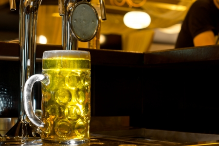 Large glowing glass tankard of golden draught beer standing on a wooden counter in a bar alongside a row of stainless steel taps for dispensing the beer in a nightclub photo