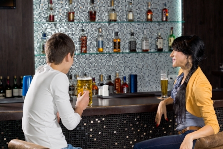 Young couple enjoying a date drinking a beer at the bar sitting at the counter chatting with a display of alcohol bottles on shelves behind them photo