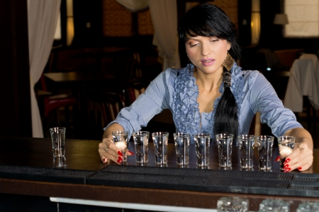 aligning: Attractive brunette hostess aligning shot glasses on the bar in a fancy location Stock Photo