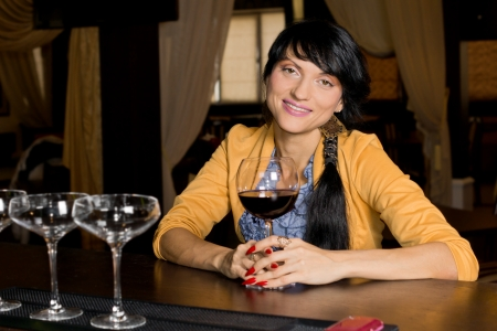 Horizontal portrait of a trendy young pretty brunette woman smiling relaxed while holding a saucer glass of red wine at the bar photo