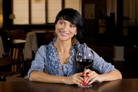 Flirtatious young woman drinking at a bar turning to give a big inviting smile to another customer as she holds a large glass of red wine photo