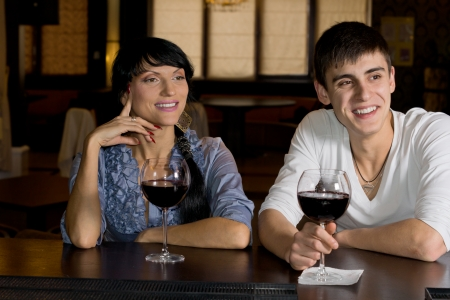 Happy young couple drinking red wine at the bar smiling in amusement as they watch something off screen to the right photo