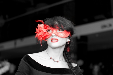 Nonconformist seductive young brunette woman wearing red lipstick and a red spectacular floral Venetian masquerade eye mask in a crowded hall photo